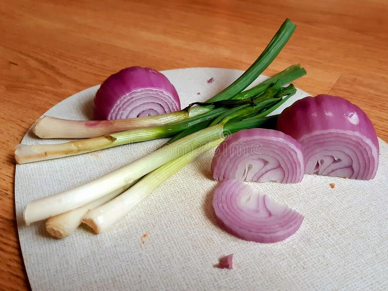 Onions on cutting board. Green and red onions on a cutting board stock photography