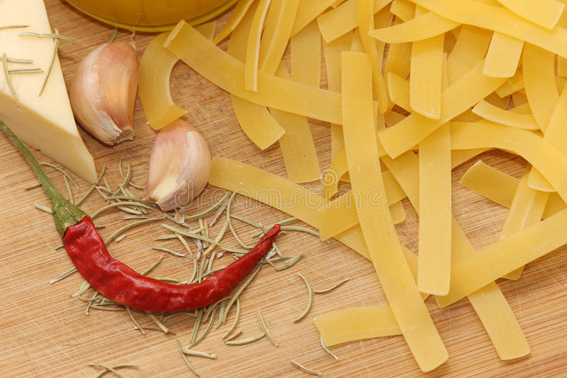 Onions, peppers, cheese and pasta. Onions, pepper, cheese pasta on a wooden board royalty free stock photos