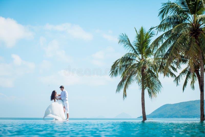 Onlangs echtpaar na huwelijk in luxetoevlucht Het romantische bruid en bruidegom ontspannen dichtbij zwembad honeymoon stock foto