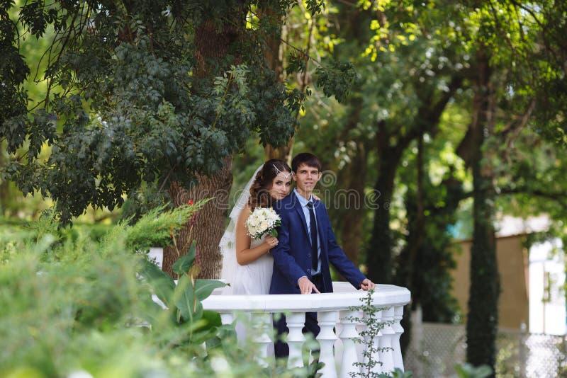 Onlangs echtpaar stellen die zich op een wit balkon in de tuin bevinden De bruid kwam erachter aan de bruidegom uit stock fotografie