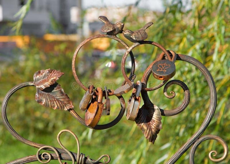Onlangs gehuwd park Twee cooing vogels en de bruid en bruidegomhangsloten op de rug van een smeedijzerbank, symbool van eeuwige l royalty-vrije stock foto