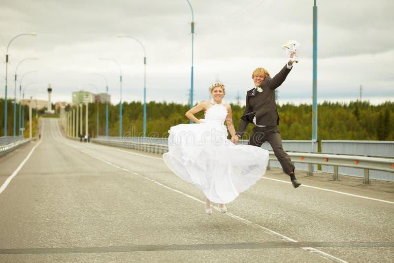 Onlangs gehuwde paarsprongen op weg royalty-vrije stock fotografie