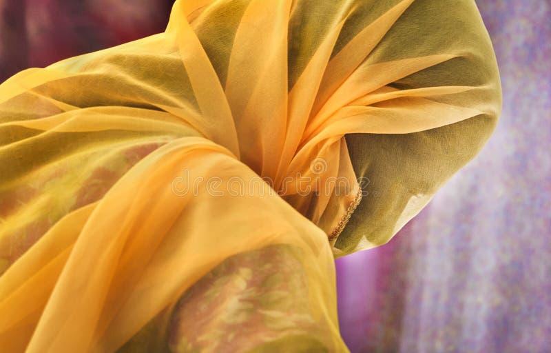 Onlangs gehuwde vrouw die oranje sjaal dragen die zijn geheel hoofd behandelt stock afbeelding