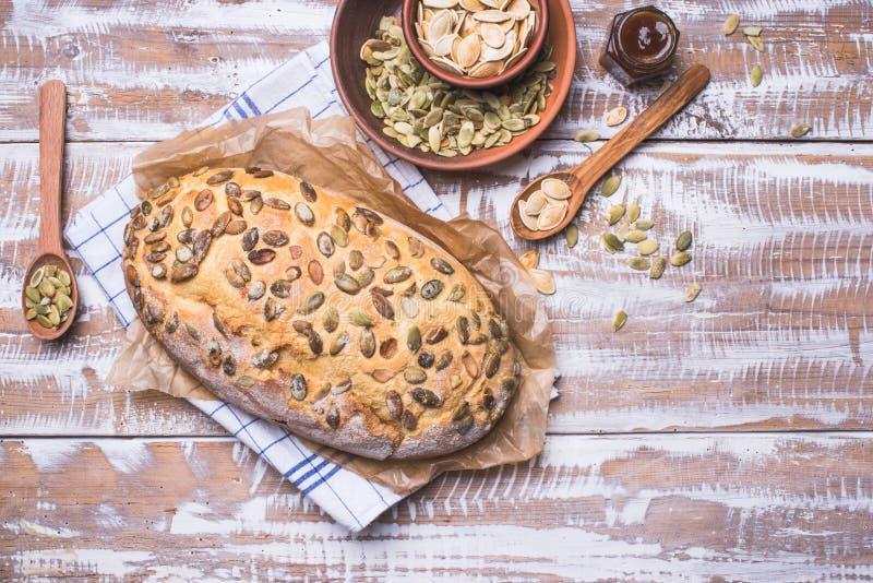 Onlangs grootgebracht brood met pompoenzaden op houten lijst royalty-vrije stock foto