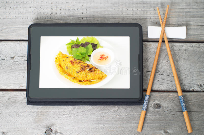 Online asian food ordering concept. With a pair of chopstick and a tablet stock photography