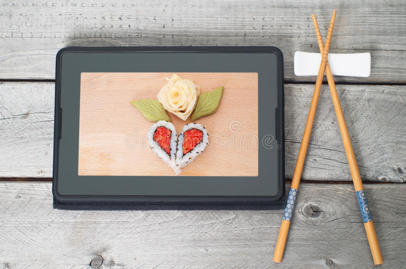 Online asian food ordering concept. With a tablet and pair of chopsticks royalty free stock images