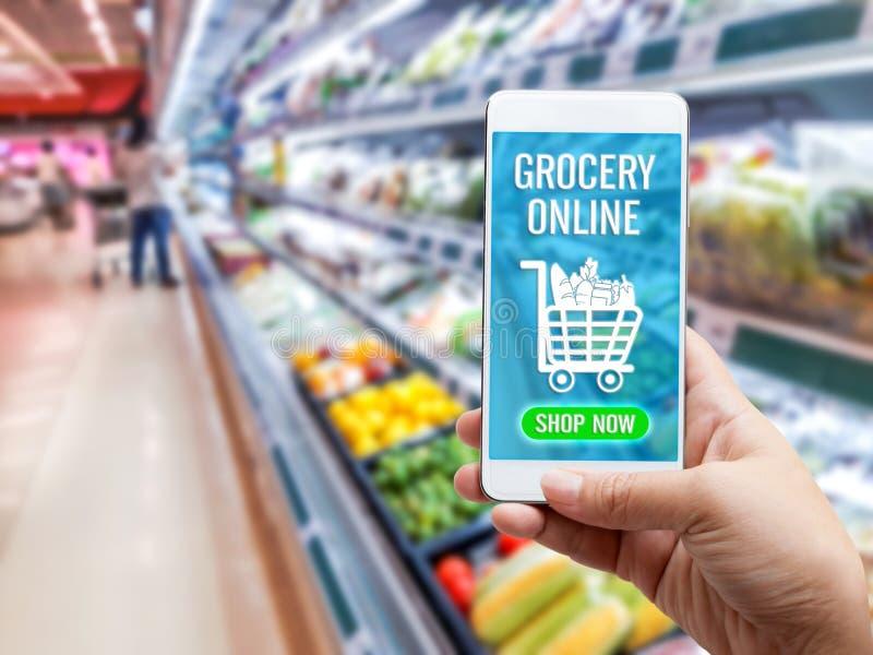 Online-begrepp f?r livsmedelsbutikshopping: Kvinnahand som rymmer den smarta telefonen f?r att best?lla mat onscreen med symbolsm royaltyfri bild
