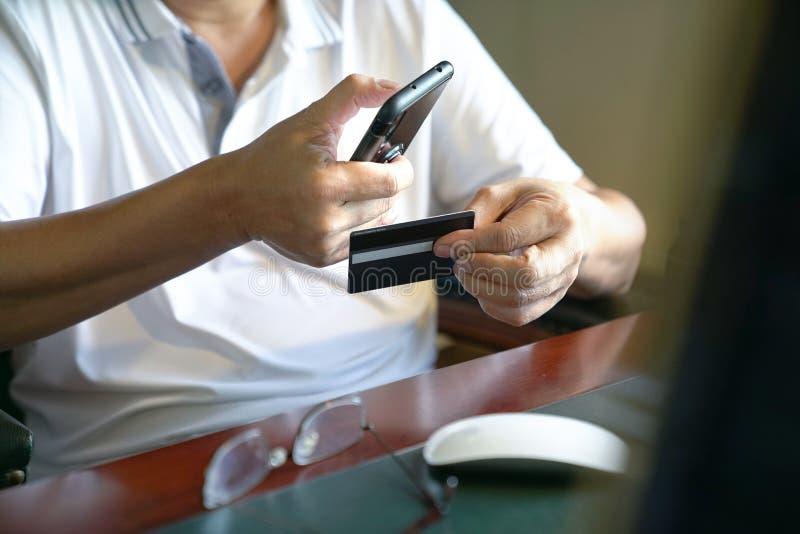 Online-betalning: Man som rymmer en smart telefon och kreditkort som är klara att göra ett köp arkivfoto