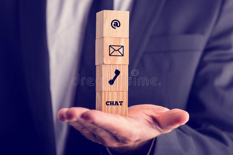 Online business communications concept. With a businessman holding a stack of four wooden cubes balanced on his palm displaying icons for email, a web address royalty free stock photography