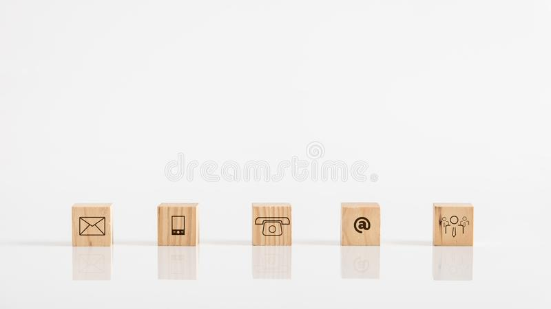 Online business communications concept of wooden cubes on white. Table displaying icons for email, a web address, mail, telephone and human icon stock image