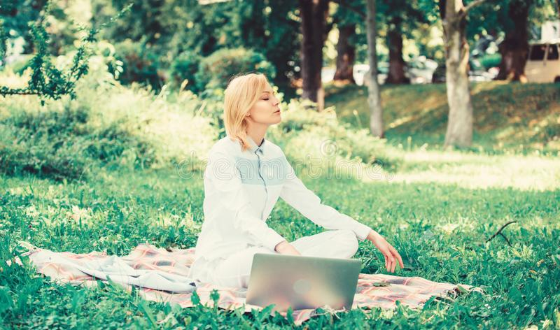 Online business ideas concept. Woman with laptop or notebook sit on rug green grass meadow. Business lady freelancer. Work outdoors. Business picnic concept stock photo