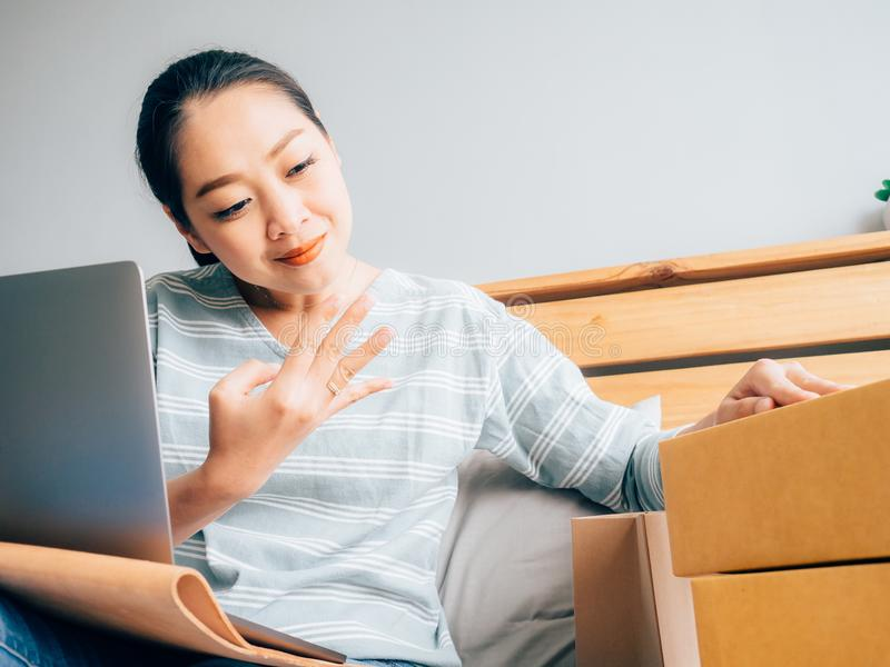 Online business owner woman receive customer order and checking. Online business owner Asian woman receive customer order and checking her product stock stock photo