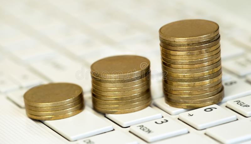 Online business success, money coins stacks. On a computer keyboard royalty free stock photos