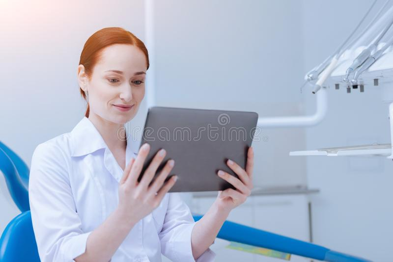 Cheerful medical worker looking at the tablet. Online call. Attentive female holding tablet in both hands and smiling while looking downwards stock image