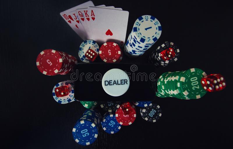 Online casino gambling concept. Smartphone blank screen on chips stack, royal flush poker cards combination and red dices and royalty free stock images