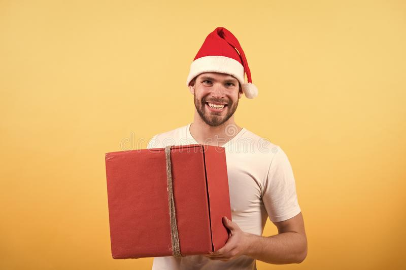 Online christmas shopping. Happy new year. happy santa man on yellow background. man in santa hat hold christmas present stock images