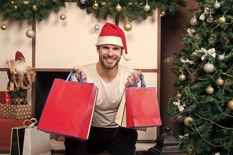 Online christmas shopping. New year scene with tree and gifts. man in santa hat hold christmas present. happy santa man stock images