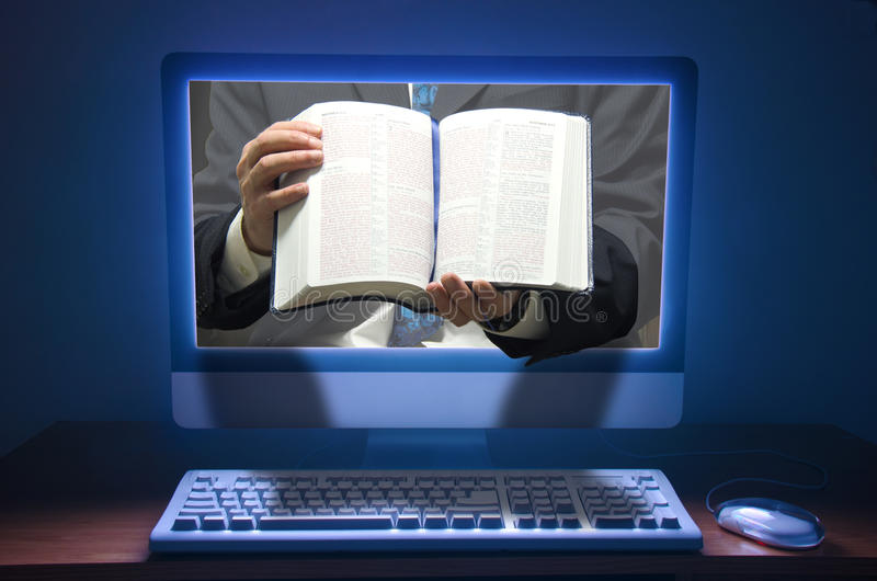 Online church ministries, mass, Bible studies. Online church concept showing a preachers hands holding a Bible coming out of a computer screen with dramatic royalty free stock photos