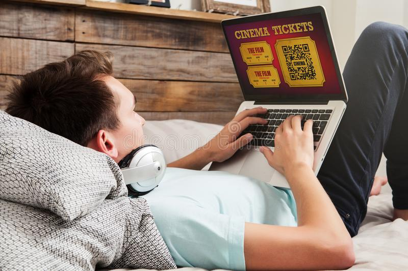 Man buying on line cinema tickets on the internet with a laptop computer, while lying down on the bed at home. royalty free stock photography