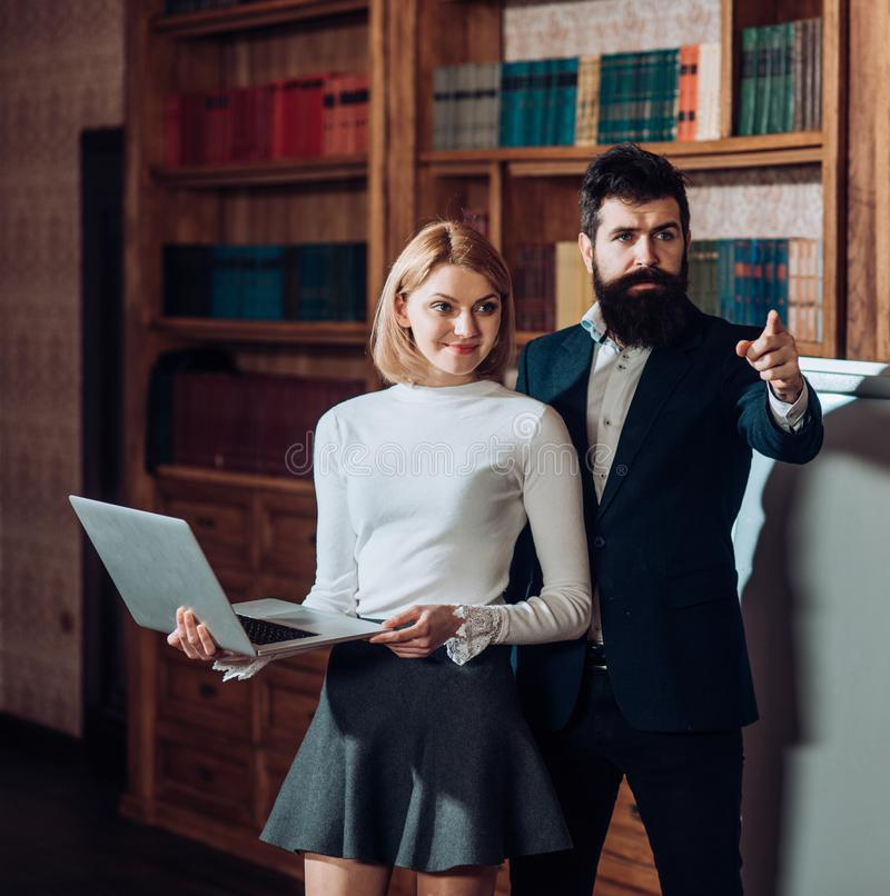 Online concept. Bearded man and sensual woman use digital library online in laptop. University online education and royalty free stock photo