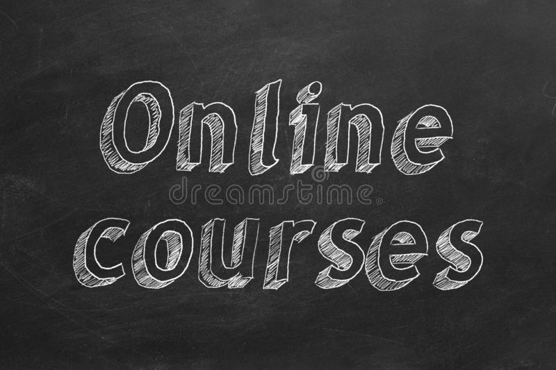 Online courses. Hand drawing `Online courses` on black chalkboard royalty free illustration