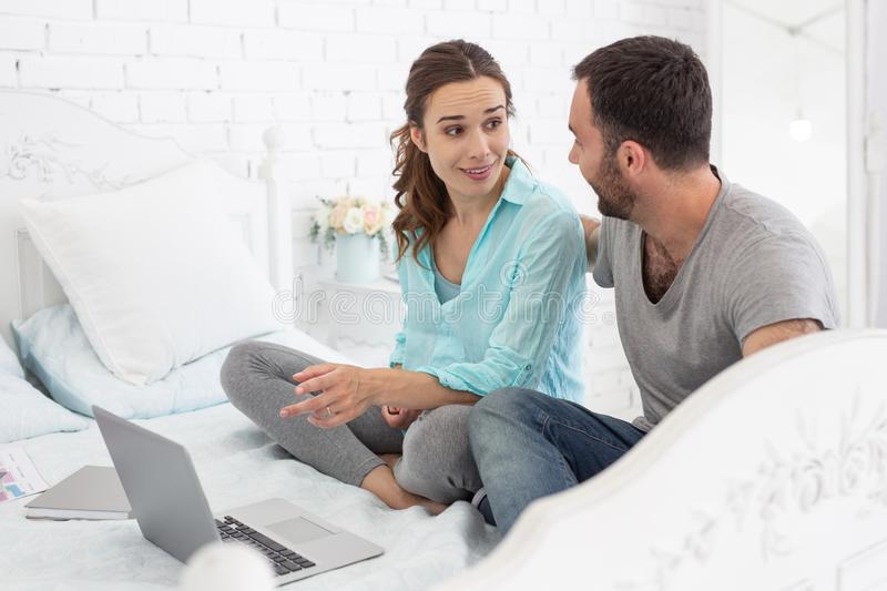 Adorable pregnant woman and man enrolling courses. Online courses. Top view of amazed pregnant women and men looking at each other and using laptop royalty free stock photos