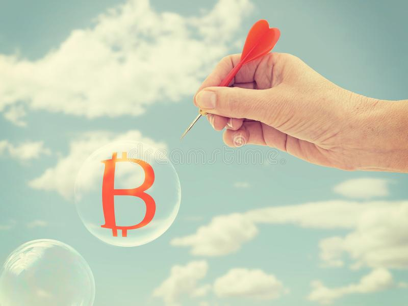 Bitcoin bubble about to burst,hand with dart. Risk. royalty free stock photography