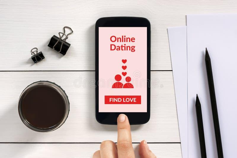 Online-datera app som är falsk upp på den smarta telefonskärmen med kontorsobje royaltyfria foton