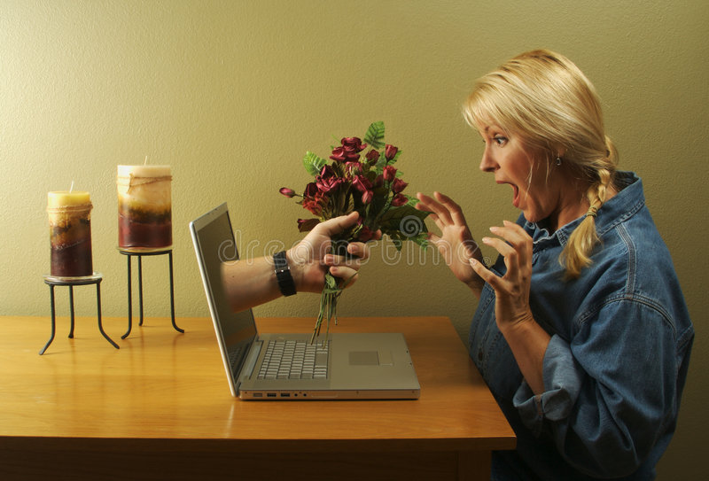Online Dating. Attractive woman stunned from the flower handed to her coming through her laptop screen