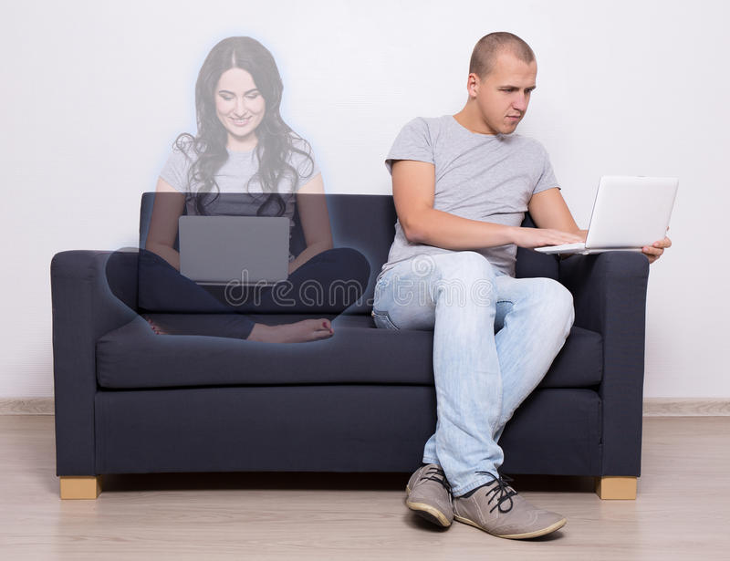 Online dating concept - handsome man sitting on sofa and chatting with imaginary girl. Online dating concept - handsome men sitting on sofa with laptop and stock photo