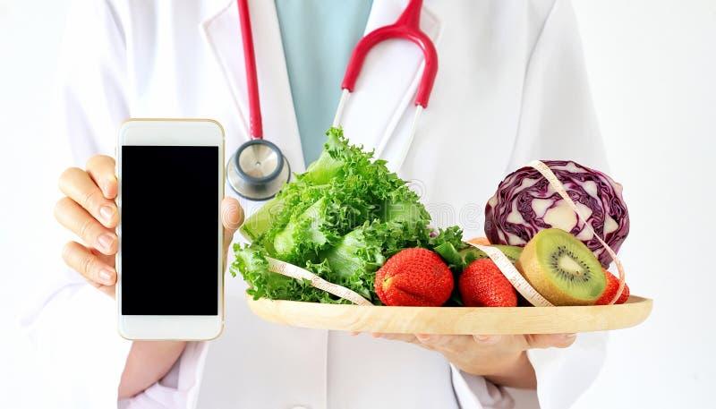 Online dieetadviseur, Arts die slimme telefoon, vers fruit houden stock foto