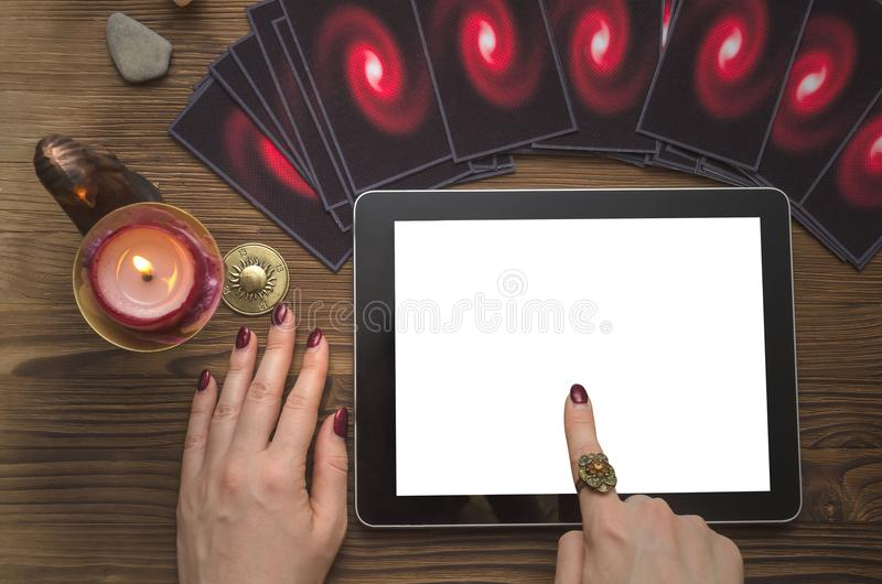 Tarot cards deck. Future reading. Fortune teller. The psychic. Online future reading concept. Tarot cards and tablet computer with blank screen on fortune royalty free stock images