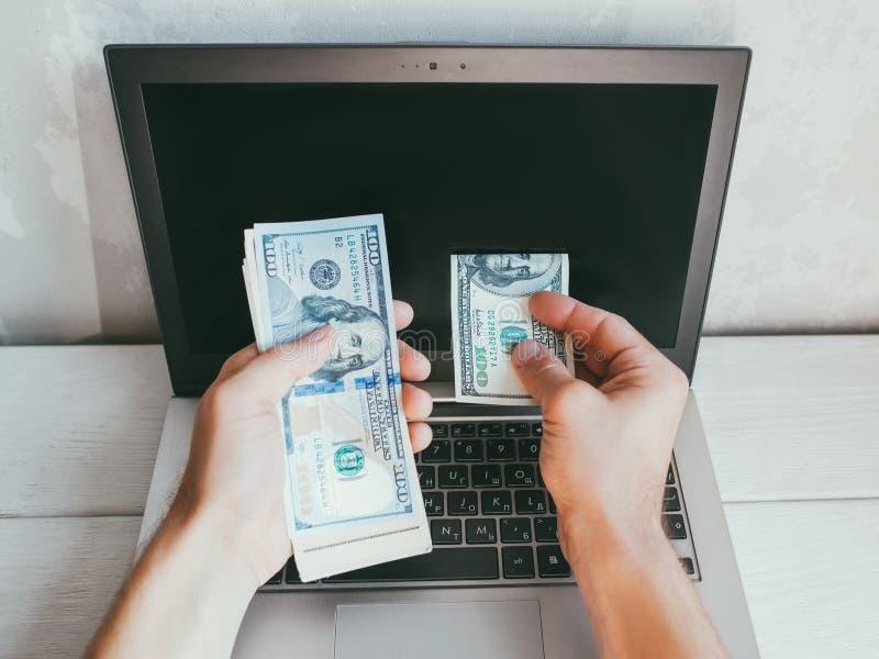 Online-Glücksspiel 100-Dollar-Scheine Laptop-Wette stockfotos