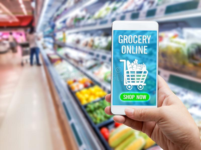 Online grocery shopping concept: Woman hand holding smart phone for ordering food onscreen with icon media on supermarket royalty free stock image