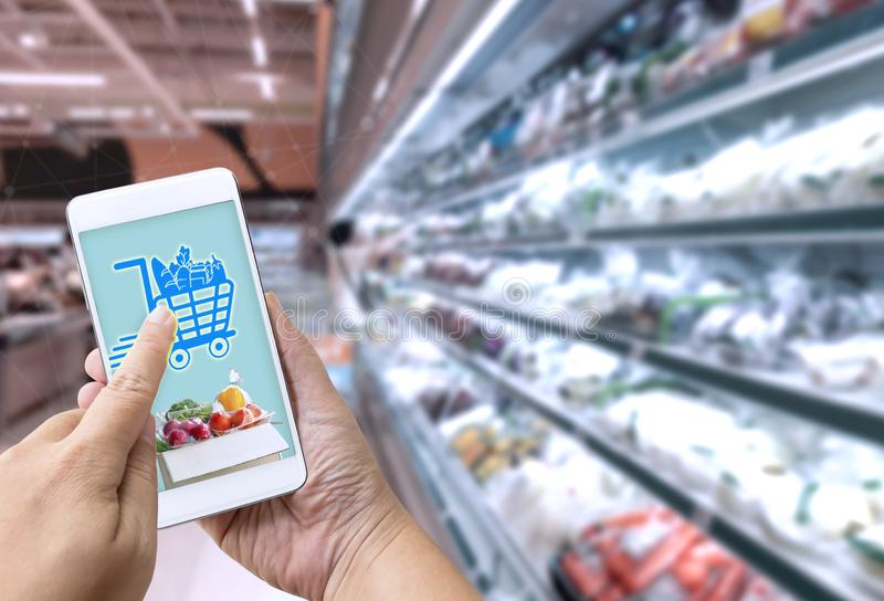 Online grocery shopping concept: Woman hand holding smart phone for ordering food onscreen with icon media on supermarket stock photo