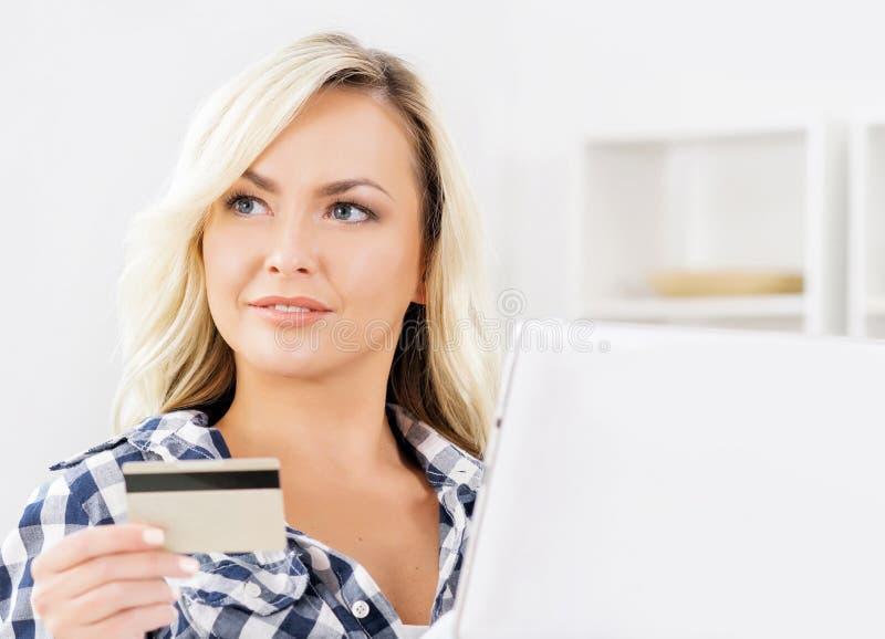 Online het winkelen concept Mooi blond meisje met een creditcard royalty-vrije stock fotografie