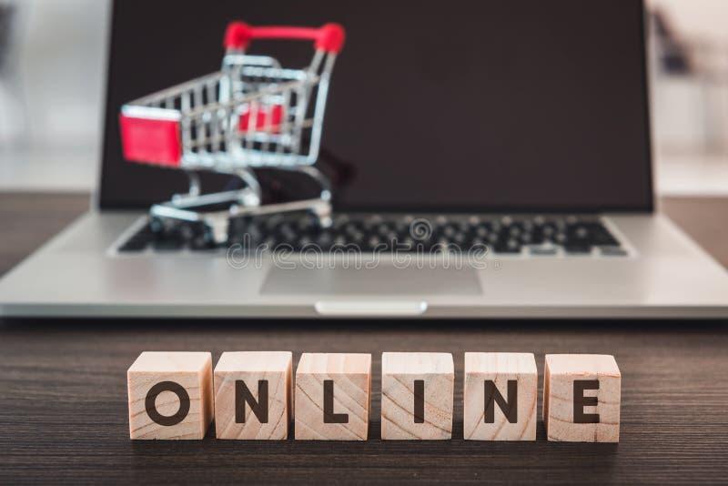 Online het Winkelen en van de Bedrijfs het Concept Ontwikkelingse-commerce , Rij van Houten Kubus met Tekst die voor Computerlapt stock foto