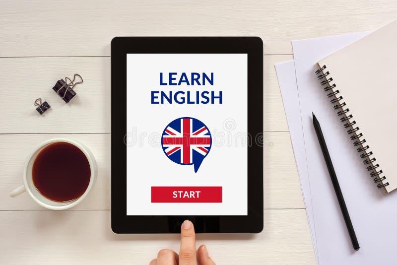 Online impari il concetto inglese sullo schermo della compressa con l'oggetto dell'ufficio immagini stock