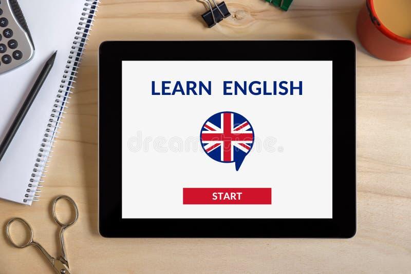 Online impari il concetto inglese sullo schermo della compressa con l'oggetto dell'ufficio fotografia stock