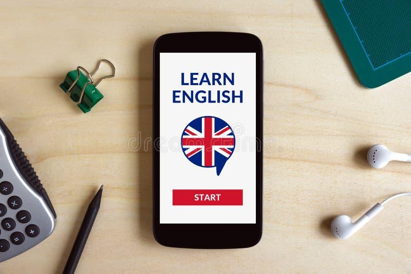Online impari il concetto inglese sullo schermo dello Smart Phone sullo scrittorio fotografie stock