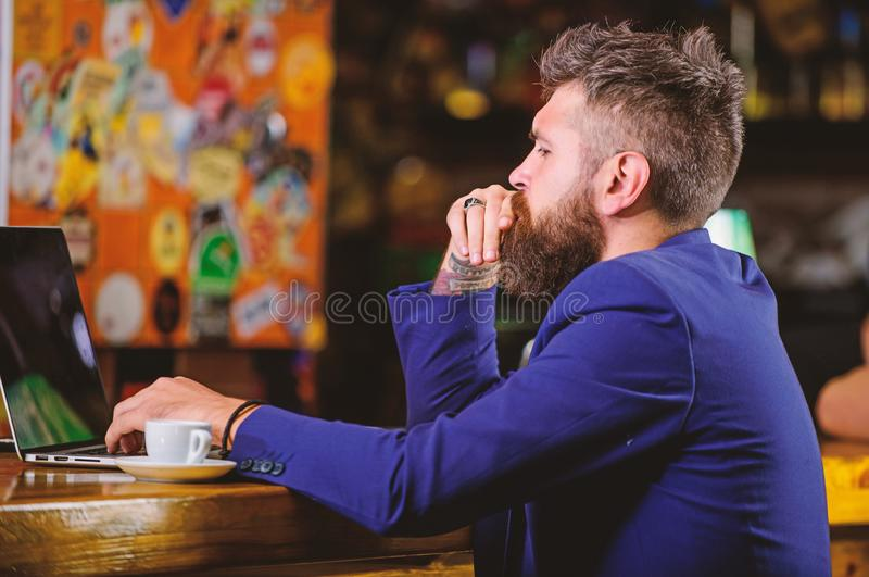 Online job. Hipster freelancer work online blog notebook. Surfing internet. Freelance benefit. Man bearded businessman. Sit pub with laptop and cup of coffee royalty free stock photography