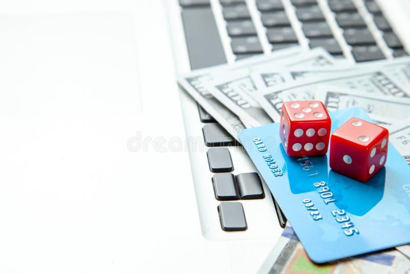 Online kasyno, online uprawia hazard Pieniędzy gotówkowi dolary i kredyta wytyczne z kostkami do gry dla hazardu na laptop klawia fotografia royalty free