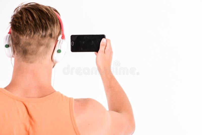 Online-kommunikation Ny teknik i modernt liv sexig muskulös man att lyssna musik mannen lyssnar den nya sången som isoleras på royaltyfri bild