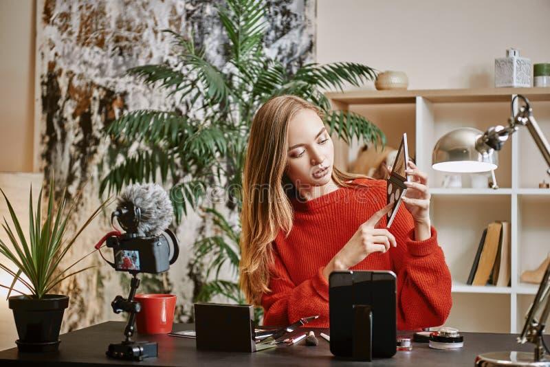 Online leerprogramma Jonge aantrekkelijke vrouw die een make-uppalet op camera tonen en nieuwe video voor haar schoonheidsblog re royalty-vrije stock fotografie
