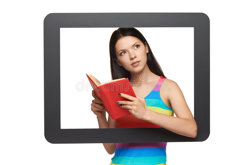 Online library concept. Pensive young woman with a book, standing behind tablet frame, over white background royalty free stock photo