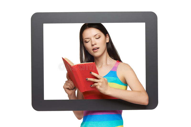 Online library concept. Young woman reading a book through tablet frame, over white background royalty free stock photography