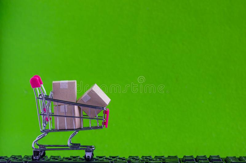 Online market place, eCommerce concept : Shopping cart with paper carton ready to shop on black keyboard Ordered by customer royalty free stock photography