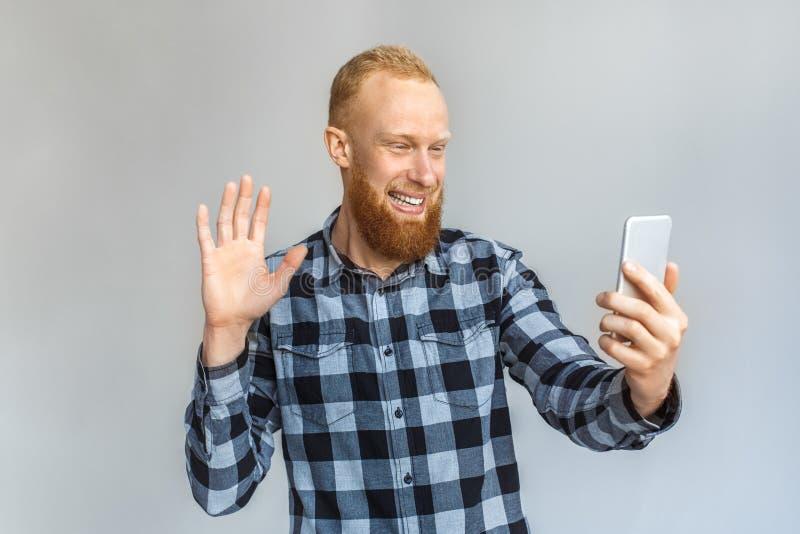 Online mededeling Rijpe mens die op grijs wordt zich geïsoleerd bevinden die die videogesprek op smartphone hebben die aan vriend royalty-vrije stock afbeelding