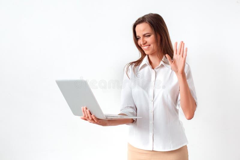 Online mededeling Vrouw die op wit wordt zich geïsoleerd bevinden die die videogesprek op laptop hebben die aan vrolijke camera g royalty-vrije stock afbeeldingen