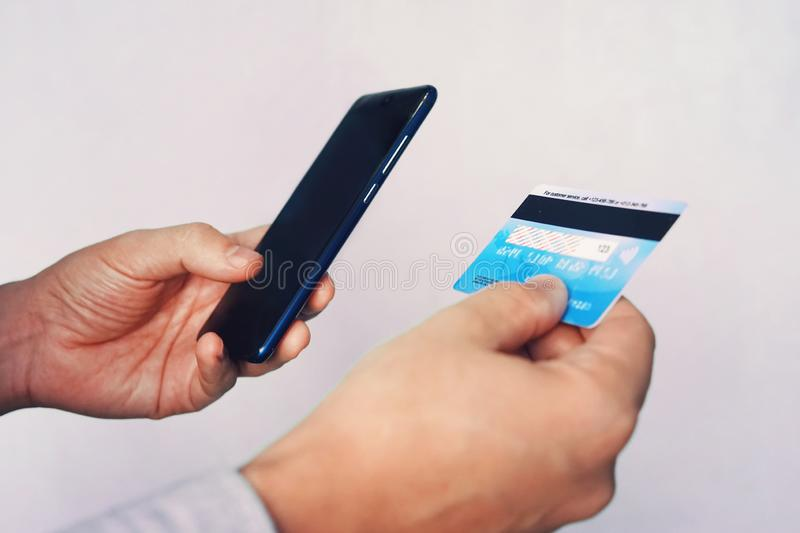 Online payment concept. Man using credit card with mobile phone at white background. Male hands holding smartphone with blank royalty free stock photos